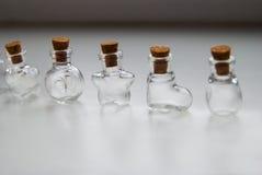 Mini Glass embotella diversas formas con el tapón del corcho en el fondo blanco Fotografía de archivo