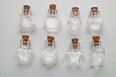 Mini Glass embotella diversas formas con el tapón del corcho en el fondo blanco Foto de archivo libre de regalías