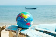 Mini globe on a boat on the ocean background. Toy globe shot close-up, lies on a boat against the background of the Indian Ocean Stock Images