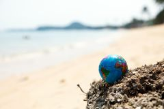 Mini globe in stone. Small earth globe lies on a rock on a tropical beach stock image