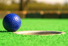 Mini Golf. A golf ball resting just on the edge of the hole Royalty Free Stock Image