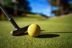Mini Golf amarela a bola com um bastão no por do sol Imagem de Stock Royalty Free