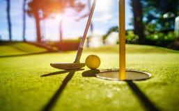 Mini Golf amarela a bola com um bastão perto do furo no por do sol Imagens de Stock Royalty Free