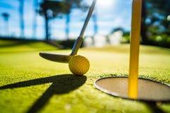 Mini Golf amarela a bola com um bastão perto do furo no por do sol Fotos de Stock Royalty Free