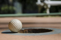 Mini Golf. A (mini) golf ball on the edge of the hole just a moment away from falling in it Stock Image