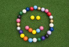 Mini Golf Ball Happy Face. Happy face formed with colorful mini golf balls on artificial grass royalty free stock photo