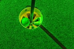 Mini golf ball inside the hole. And green artificial grass stock images