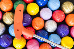 Mini Golf Balls and Club. Assorted Mini Golf balls with an orange club Royalty Free Stock Photography