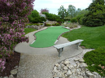 Mini Golf Hole. Mini Golf Course Hole with Trees, Flowers, and Waterfall Royalty Free Stock Image
