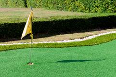Mini golf with hole on green and flag. In the evening Royalty Free Stock Photography