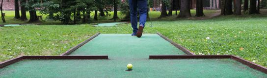 Mini-golf player goes for a kick, close-up royalty free stock image