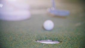 Mini Golf Una persona que golpea la bola y lo consigue en el agujero almacen de metraje de vídeo