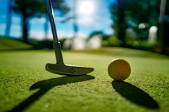 Mini Golf yellow ball with a bat near the hole at sunset. Mini Golf yellow ball with a bat near hole at sunset royalty free stock photo