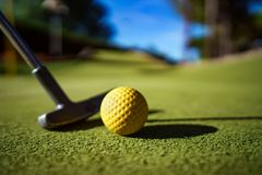Mini Golf yellow ball with a bat at sunset Royalty Free Stock Image