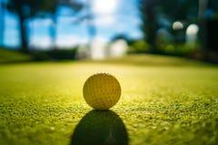 Mini Golf yellow ball on green grass at sunset. Goif stock photos
