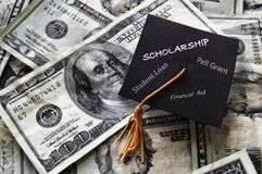 Financial Aid concept. Mini graduation cap on cash with assorted education financial assistance related text Stock Photography