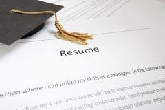 Resume. Mini graduation cap on a job hunters resume royalty free stock image