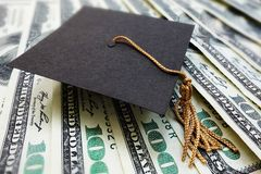 Graduation cap on money. Mini graduation mortar board cap on money -- education cost or scholarship concept Stock Images