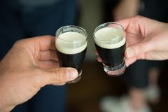 Mini guiness beer cheers. Two person cheering with their mini glass of guiness beer Stock Image