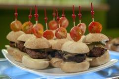 Mini- hamburgare med den körsbärsröda tomaten royaltyfria bilder