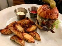 Mini Hamburger med potatiskilar tjänade som med ketchup och majonnäs arkivbild