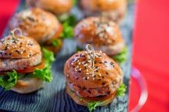 Mini-hamburgers faits maison savoureux sur la fin de conseil en bois photo stock