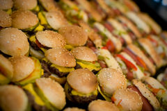 Mini hamburgers and hotdogs. Mini hamburgers and hot dogs with cheese and sesame seeds Stock Photography
