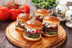 Mini hamburgers. With tomato and cucumber on wooden board Royalty Free Stock Image