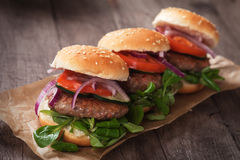 Mini hamburgers. With tomato and onion on wooden table Royalty Free Stock Images