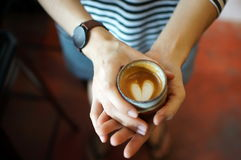 Mini heart in her hand. Beautyful cup in hand royalty free stock photography