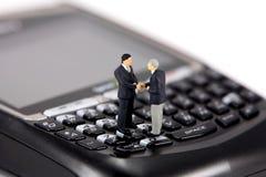 Mini hombres de negocios en el teléfono celular Fotografía de archivo