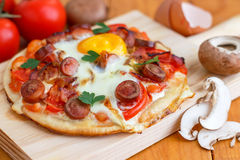 Mini Homemade Breakfast Pizza. Breakfast pizza with bacon, mushrooms, beans and eggs is the way to start your day Royalty Free Stock Photo
