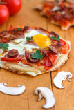 Mini Homemade Breakfast Pizza. Breakfast pizza with bacon, mushrooms, beans and eggs is the way to start your day Stock Photography