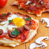 Mini Homemade Breakfast Pizza. Breakfast pizza with bacon, mushrooms, beans and eggs is the way to start your day Stock Photo