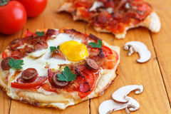 Mini Homemade Breakfast Pizza. Breakfast pizza with bacon, mushrooms, beans and eggs is the way to start your day Royalty Free Stock Images