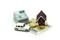 Mini House med bunten av mynt och bilen, besparing och investeramone royaltyfria bilder