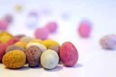 Mini huevos de chocolate del caramelo en una superficie blanca Imagen de archivo