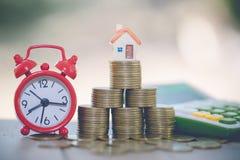 Mini- hus på bunten av mynt, begrepp av investeringegenskapen, investeringrisken och osäkerhet i fastighetbostadsmarknaden royaltyfri bild