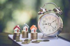 Mini- hus på bunten av mynt, begrepp av investeringegenskapen, investeringrisken och osäkerhet i fastighetbostadsmarknaden arkivbilder