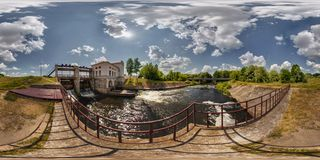 Mini hydro power plant on the lake on a sunny day. Full 360 degree panorama in equirectangular spherical projection royalty free stock photography