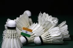 Mini India flag stick on the heap of used shuttlecocks on green floor of Badminton court. With dark black background royalty free stock photo