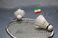 Mini Iran flag stick on the shuttlecock and another shuttlecock put on the net of badminton racket. On grey floor stock image