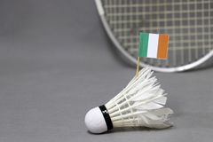 Mini Ireland flag stick on the white shuttlecock on the grey background and out focus badminton racket. Concept of badminton sport stock photo