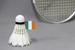 Mini Ireland flag stick on the white shuttlecock on the grey background and out focus badminton racket. Concept of badminton sport royalty free stock images