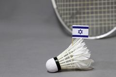Mini Israel flag stick on the white shuttlecock on the grey background and out focus badminton racket. Concept of badminton sport stock image