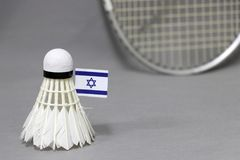 Mini Israel flag stick on the white shuttlecock on the grey background and out focus badminton racket. Concept of badminton sport stock photos