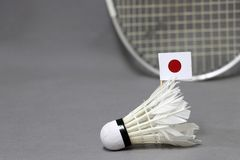 Mini Japan flag stick on the white shuttlecock on the grey background and out focus badminton racket. Concept of badminton sport stock photos