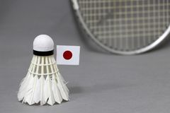Mini Japan flag stick on the white shuttlecock on the grey background and out focus badminton racket. Concept of badminton sport royalty free stock photography