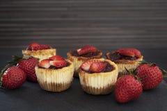Mini- jordgubbeostkaka i muffinformer royaltyfri foto