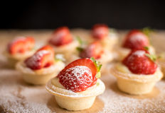 Mini- jordgubbetarts på wood bakgrund Royaltyfri Bild